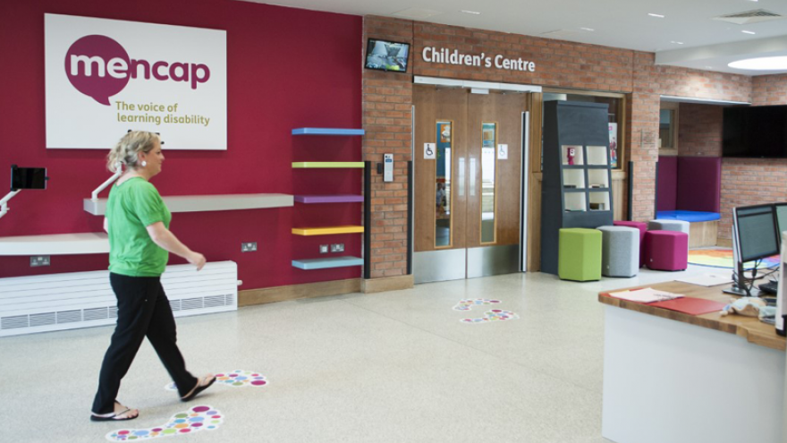 Woman walking through Mencap Centre in Belfast
