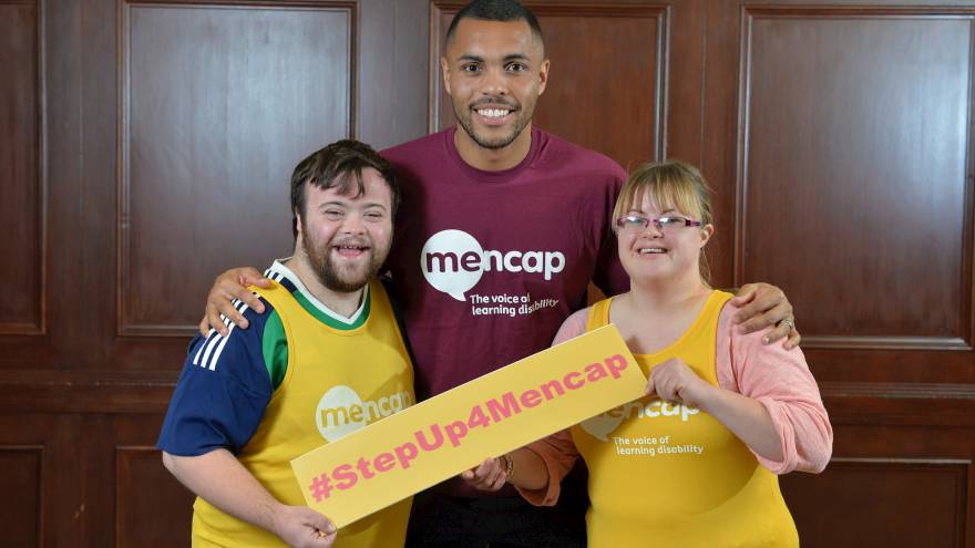 People stood together holding a #StepUp4Mencap sign
