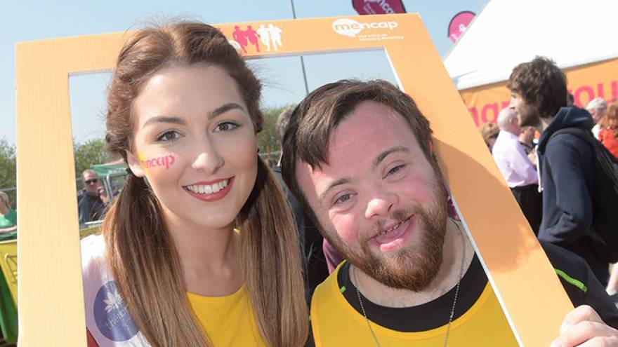 Man and woman stood together smiling with Mencap frame around their heads.