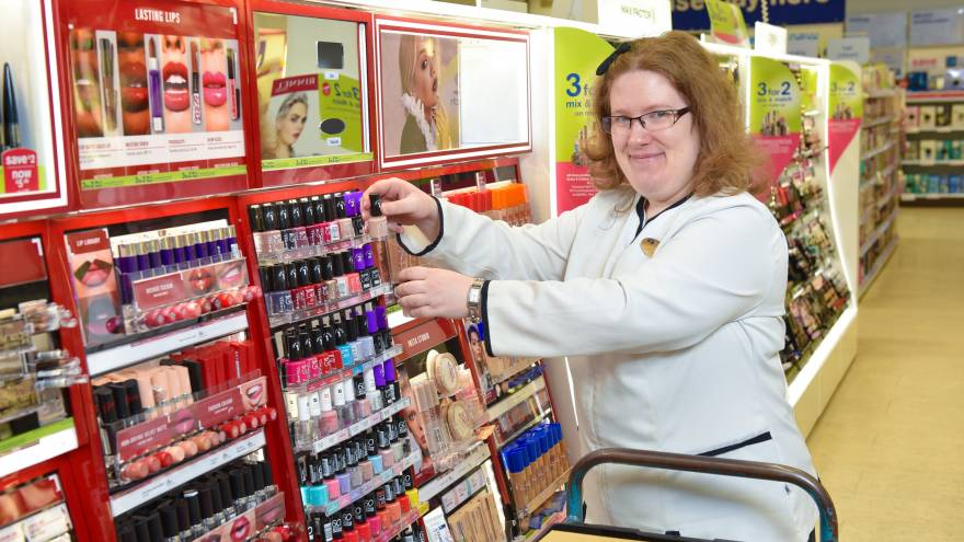Woman wearing work uniform restocking make-up items in pharmacy.