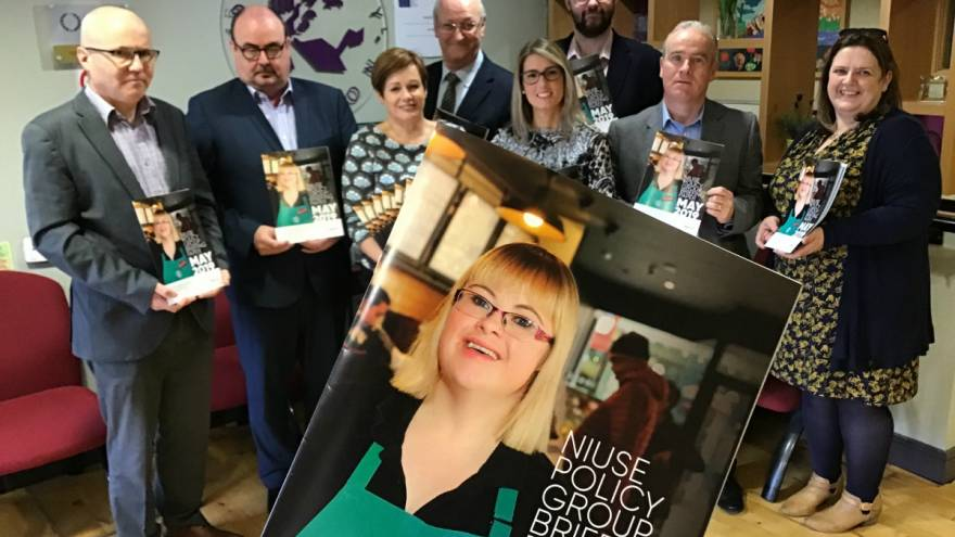Group of people holding large copy of NIUSE - Future Funding for Disability Employment Services booklet with young woman's face on it.