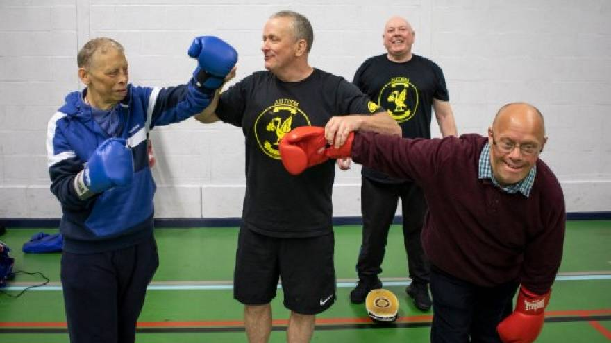 Group of men boxing in sports hall