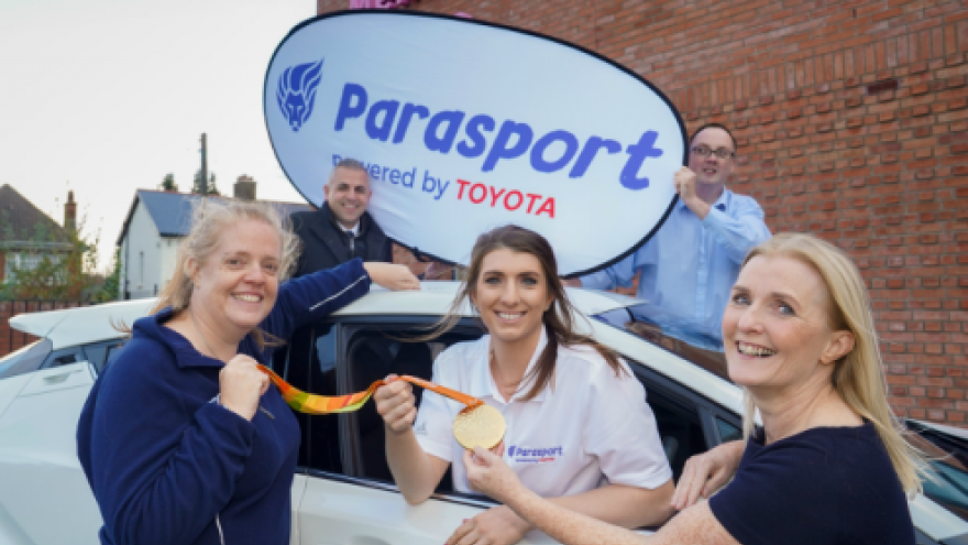"People stood together around a car, people in the background holding a ""Parasport sponsored by Toyota"" sign"