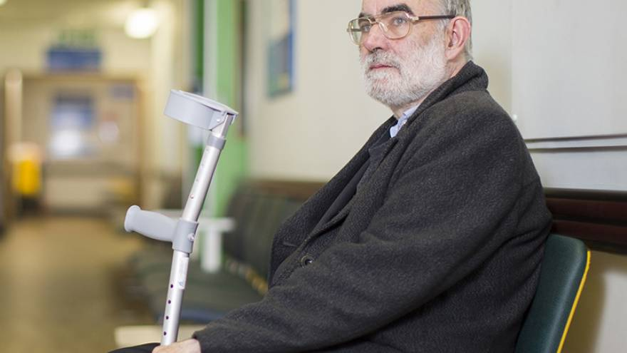 Old man holding crutches sat in hospital waiting room