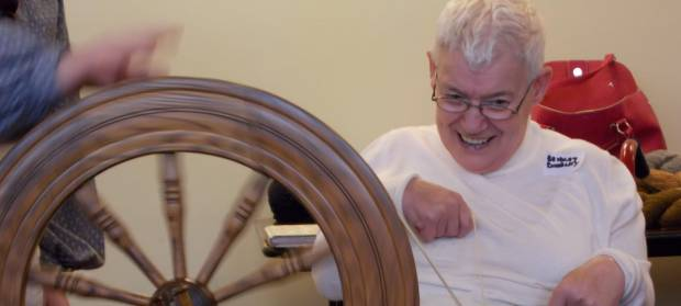 Person in white top, smiling whilst using a spinning wheel