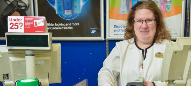 Woman wearing uniform sat at till in pharmacy.