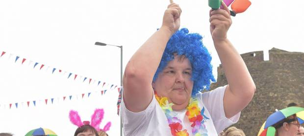 Person wearing bright blue wig waving their hands above their head, taking part in a parade.