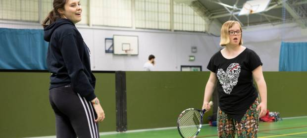 Two young women stood together in sport hall playing tennis